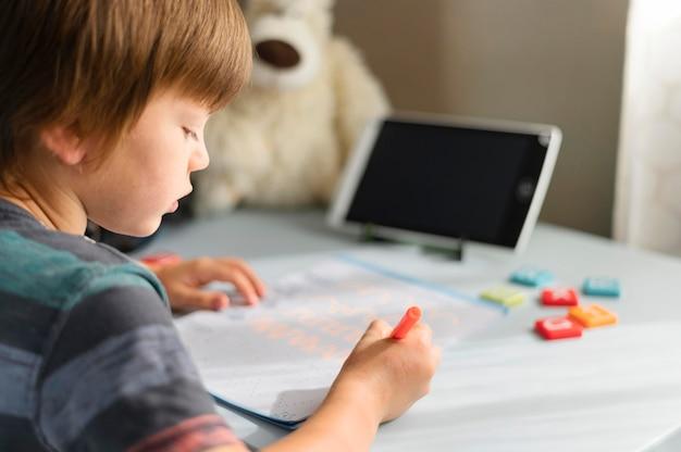 Enfant écrivant des interactions scolaires en ligne