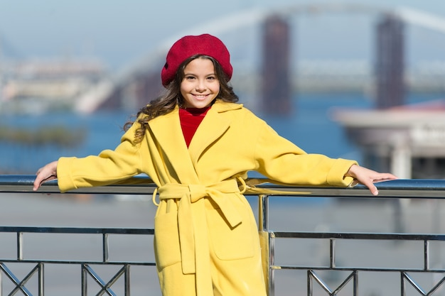 Enfant élégant en béret et manteau parisien. petite fille en plein air. un temps de printemps. tendance automne. petite fille heureuse. regard de mode d'enfant. petite femme d'affaires. petite beauté élégante. fille à la mode.