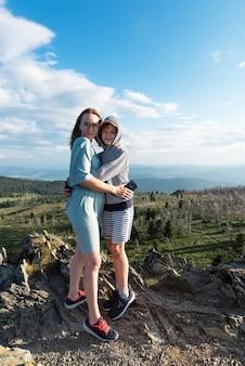 Un enfant embrasse maman dans le voyage en montagne