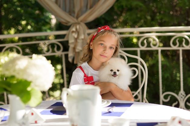 Un enfant embrasse son chien avec amour. la blonde en robe rouge avec un chien blanc.