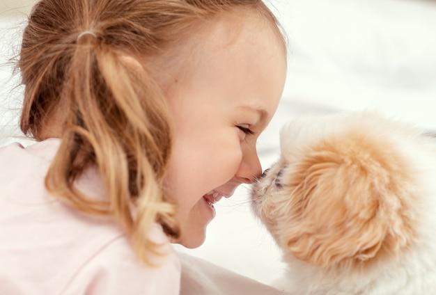 Enfant émotif et enfant de chien de bébé jouent avec le chiot sur le lit à la maison l'amitié entre l'animal et l'enfant