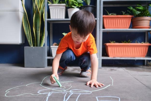 Enfant enfant garçon asiatique dessin à la craie de couleur au garage à la maison
