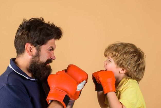Enfant d'entraînement de boxe dans des gants de boxe s'entraînant avec son entraîneur ring de boxe punching knockout enfance