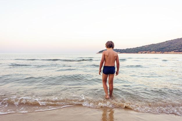 Enfant entrant dans l'eau de mer au coucher du soleil