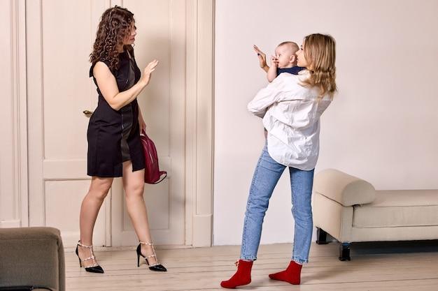 L'enfant entre les mains de la baby-sitter fait signe à sa mère de quitter
