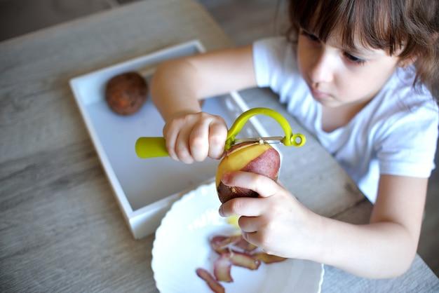 L'enfant épluche les pommes de terre avec un éplucheur vert. enfant d'âge préscolaire prépare la nourriture