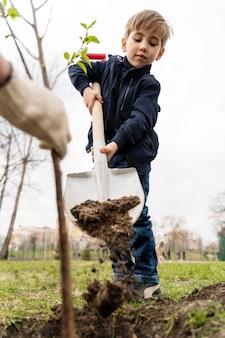 Enfant essayant de planter un arbre à l'extérieur