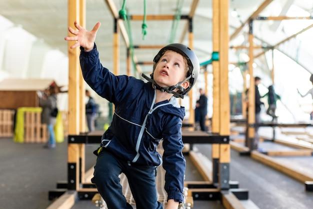 Enfant essayant de surmonter les obstacles d'un parc d'aventure.