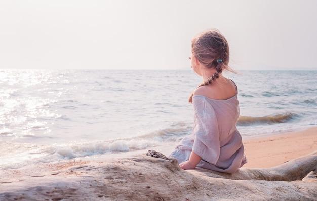 L'enfant est assis dans un arbre et regarde la mer.