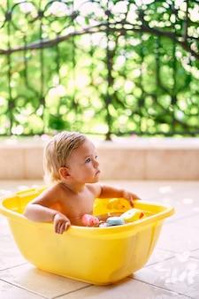 L'enfant est assis dans un bol d'eau et de jouets et lève les yeux
