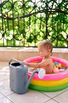 L'enfant est assis dans une mini-piscine gonflable à côté d'un arrosoir de jardin