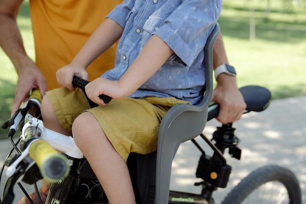 L'enfant est assis dans un siège d'enfant sur un gros plan de vélo