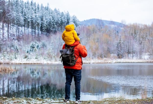 L'enfant est assis sur les épaules de son père lors d'une promenade au bord d'un lac gelé dans la forêt