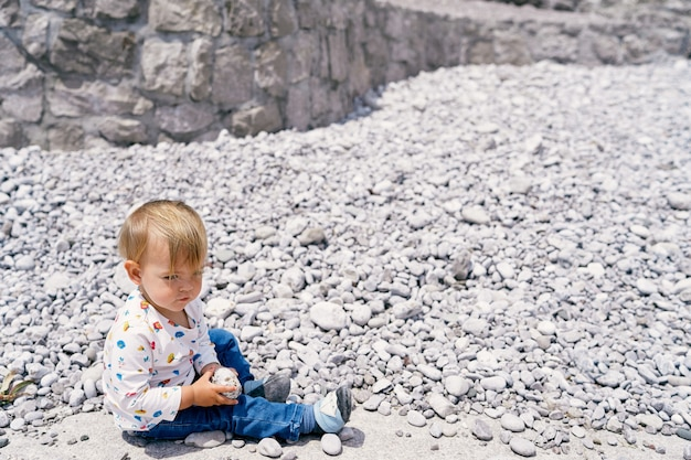 L'enfant est assis sur une plage de galets et tient un caillou dans ses mains
