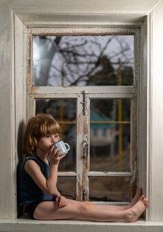 L'enfant est assis sur un rebord de fenêtre en bois minable de boire dans une tasse