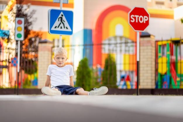 Un enfant est assis sur la route à un passage pour piétons parmi les panneaux routiers