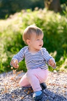 L'enfant est assis sur ses genoux tournés sur le côté et tient une brindille avec des baies