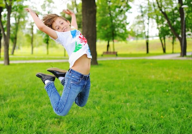 L'enfant est barbouillé de doigts colorés peignant des vêtements souriant dans le parc.