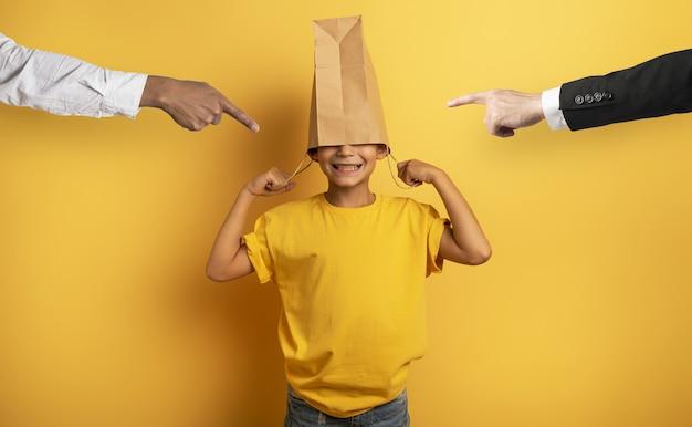 L'enfant est grondé et il cache sa tête dans un sac à provisions