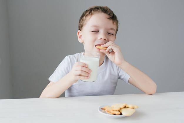 L'enfant est heureux de manger des biscuits faits maison avec du lait
