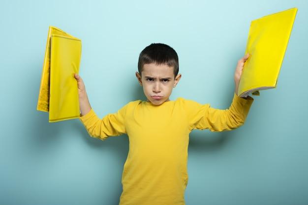 L'enfant est malheureux et en colère contre trop de surface cyan de travail scolaire