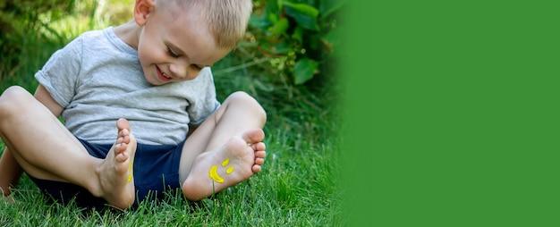 L'enfant était allongé sur l'herbe verte. souriez avec des peintures sur les jambes et les bras. enfant s'amusant à l'extérieur dans le parc du printemps. mise au point sélective. la nature