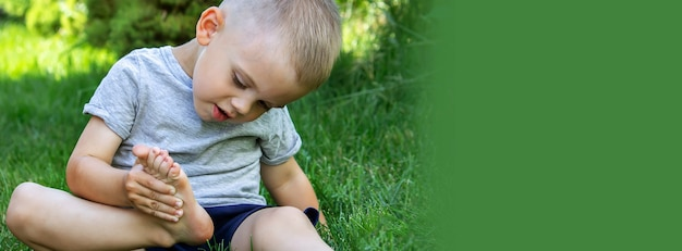 L'enfant était allongé sur l'herbe verte. souriez avec des peintures sur les jambes et les bras. enfant s'amusant à l'extérieur dans le parc du printemps. mise au point sélective.