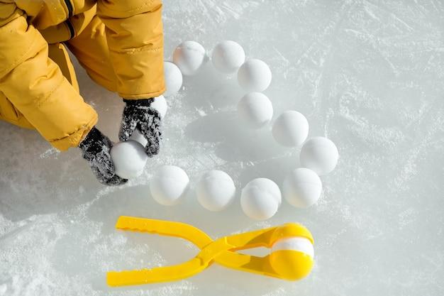Un enfant étale des boules de neige en forme de cœur sur la glace fabriquées avec un outil semblable à des pinces