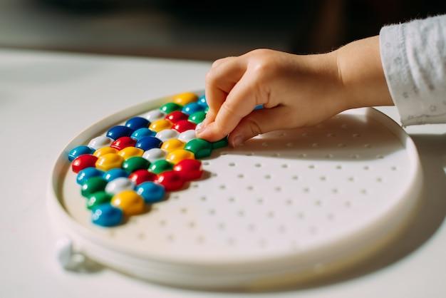 Un enfant étale une figure en mosaïque multicolore avec sa main.