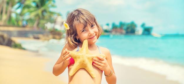 Un enfant avec une étoile de mer dans ses mains sur la plage