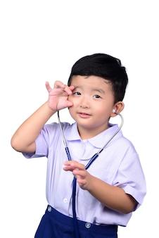 Enfant étudiant asiatique en uniforme scolaire jouant stéthoscope médical avec un tracé de détourage.
