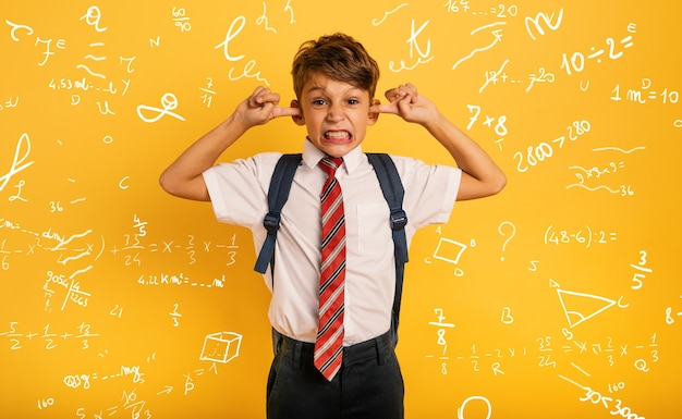 Un enfant étudiant se couvre les oreilles car il ne veut pas entendre de bruit