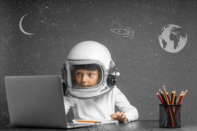 L'enfant étudie à distance à l'école, portant un casque d'astronaute. retour à l'école