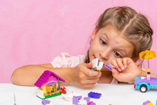 L'enfant examine un kit de construction multicolore et des cubes.
