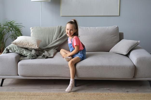 Enfant excité regardant la caméra alors qu'il était assis dans le salon à la maison.