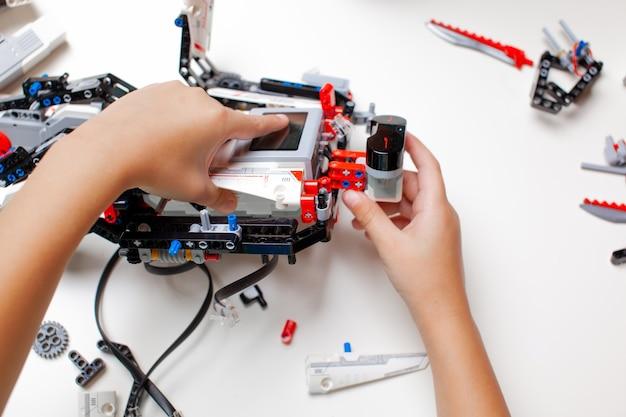 L'enfant fabrique un robot avec des pièces aléatoires