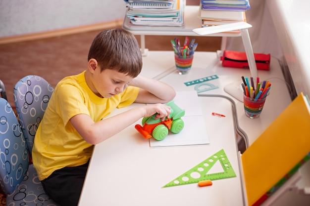 Enfant à faire ses devoirs et joue avec son jouet préféré à la maison.