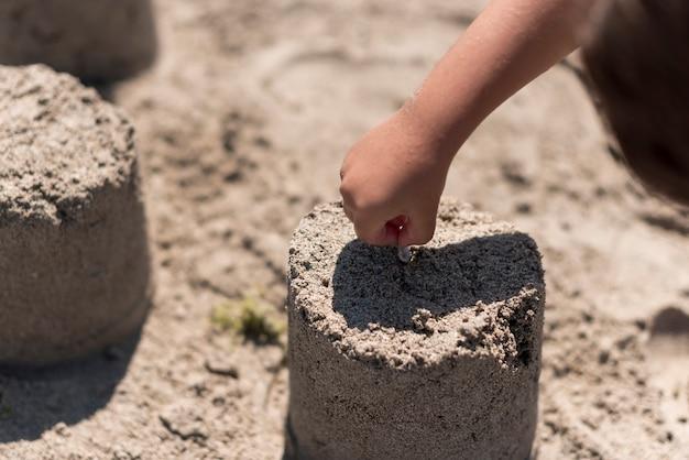 Enfant faisant un château de sable à la plage