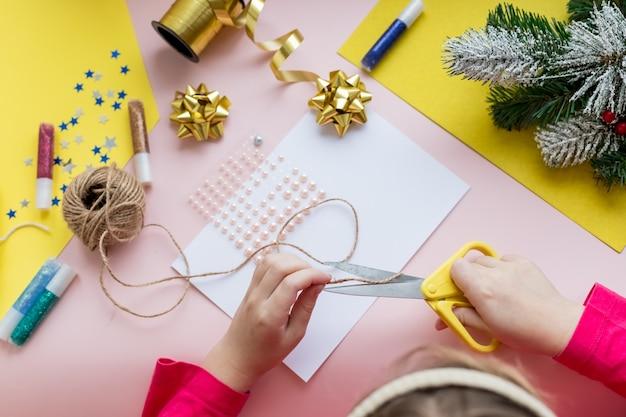 L'enfant fait une carte de noël pour les vacances d'hiver. bricolage et artisanat pour noël