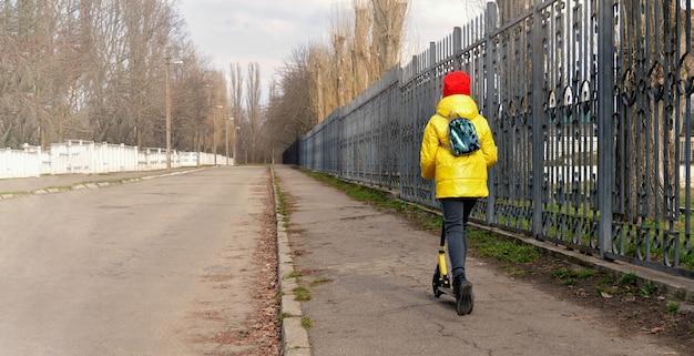 L'enfant fait du scooter. une fille en veste jaune s'éloigne en scooter dans une rue déserte le long d'une clôture en fer. espace de copie