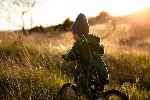 L'enfant fait du vélo d'équilibre dans le parc au coucher du soleil