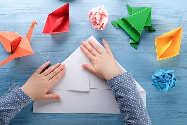 Enfant fait origami sur une table bleue