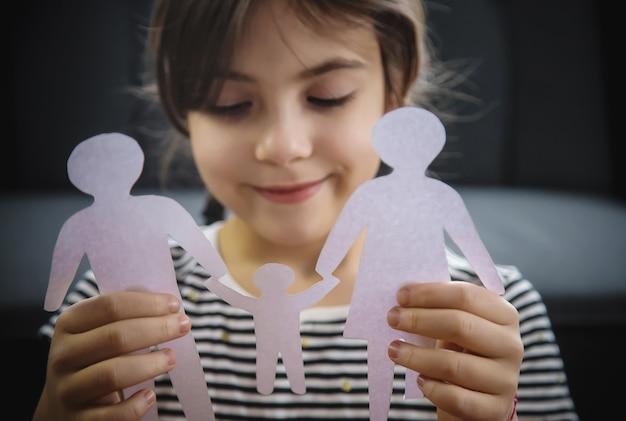 Enfant avec une famille de papier dans ses mains.