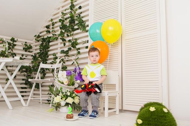 Enfant, fête d'anniversaire et concept d'enfance - petit garçon avec des ballons et des jouets à l'intérieur