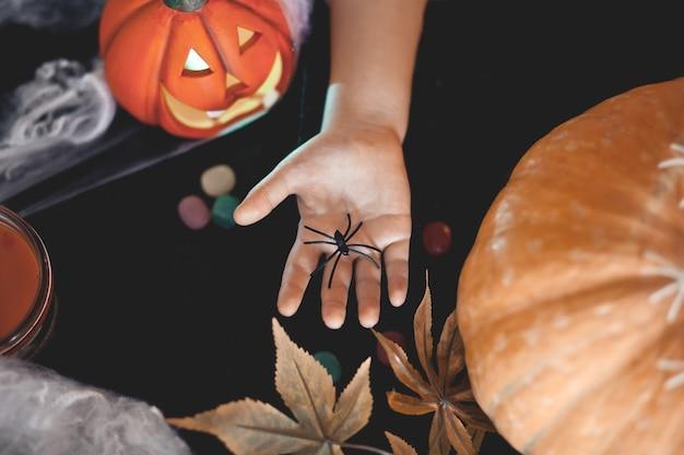 Enfant sur une fête d'halloween tenant un jouet d'araignée dans une main.