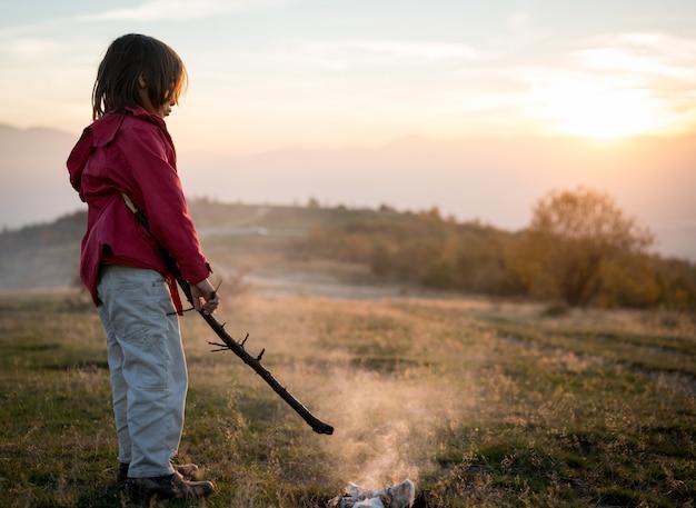Enfant avec le feu dans la nature