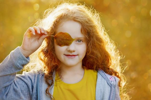 Enfant avec feuilles yeux, au repos dans le parc automne doré.