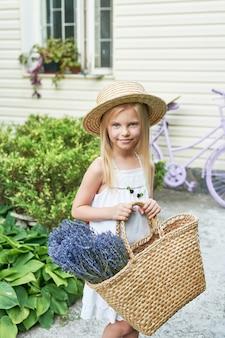Enfant fille au chapeau avec un panier de lavande dans le jardin en été