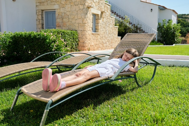 Enfant fille au repos se trouve dormir dans une chaise longue sur la pelouse.