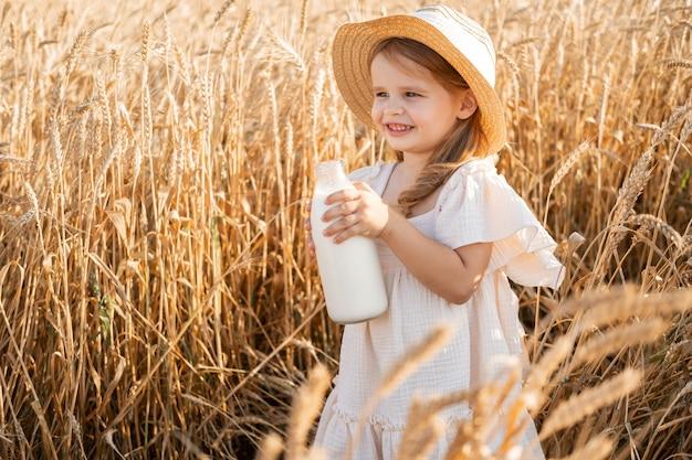 Enfant fille blonde en chapeau de paille et robe de mousseline beige tient bataille de lait dans un champ de blé au coucher du soleil.